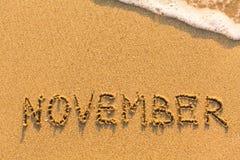 在海滩沙子-用手写的11月 免版税库存图片
