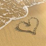 在海滩沙子画的心脏,柔和的海浪波浪 爱 库存照片