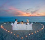 在海滩浪漫晚餐的夫妇与蜡烛心脏 免版税库存照片