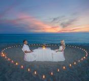 在海滩浪漫晚餐的夫妇与蜡烛心脏 图库摄影