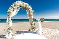 在海洋海岸的大白色婚礼曲拱 库存图片