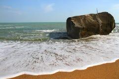 在海滩海浪的岩石 免版税库存图片