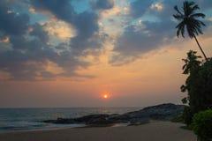 在海洋海滩上的日落反对岩石和棕榈树 免版税库存照片