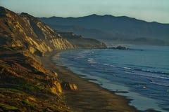在海洋海滩峭壁的日落设置 库存照片