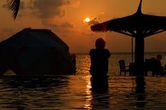 在海滩游泳池的日落 免版税库存照片
