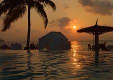 在海滩游泳池的日落 库存图片