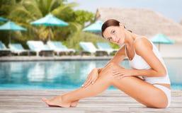 在海滩游泳池的美丽的少妇 免版税库存图片