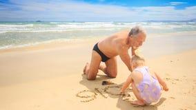 在海滩湿沙子的祖父一点白肤金发的女孩凹道由海浪的 影视素材