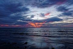 在海洋灰色云彩的火热的橙色日出 免版税库存图片