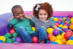 在海绵球水池的逗人喜爱的微笑的孩子 库存照片
