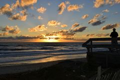 在海滩甲板的剪影日落的 免版税库存图片