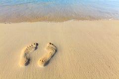 在海滩的一串对脚步 免版税库存照片