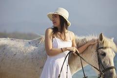 在海滩的一匹妇女走的马 免版税库存图片
