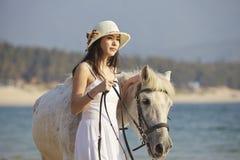 在海滩的一匹妇女走的马 库存图片