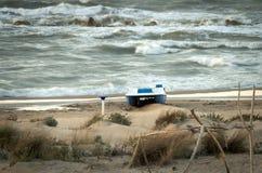 在海滩的一条小船在一多云天 免版税库存图片