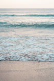 在海滩的一点波浪在日落 免版税图库摄影