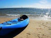 在海滩的一艘蓝色皮船 图库摄影