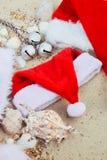 在海滩的三个圣诞节帽子 圣诞老人帽子在壳附近的沙子 家庭假日 新年假期 复制空间 框架 顶视图 免版税库存图片