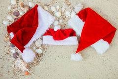在海滩的三个圣诞节帽子 圣诞老人帽子在壳附近的沙子 家庭假日 新年假期 复制空间 框架 顶视图 免版税图库摄影