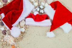 在海滩的三个圣诞节帽子 圣诞老人帽子在壳附近的沙子 家庭假日 新年假期 复制空间 框架 顶视图 免版税库存照片