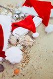 在海滩的三个圣诞节帽子 圣诞老人帽子在壳附近的沙子 家庭假日 新年假期 复制空间 框架 顶视图 库存图片