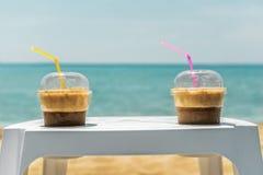 在海滩的两个冰frappe咖啡杯 免版税库存照片