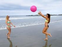 在海滩的两个年轻女性成人 库存图片