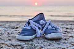 在海滩的两双运动鞋 免版税库存照片