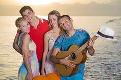 在海滩的两对愉快的夫妇在日落 免版税库存图片