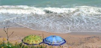 在海滩的两把五颜六色的伞 免版税库存照片