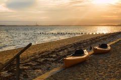 在海滩的两艘皮船在日落在鳕鱼角 库存照片