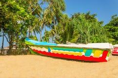 在海滩的五颜六色的异乎寻常的小船与棕榈树 库存图片