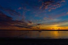在海滩的五颜六色的日落天空 免版税库存图片