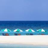 在海滩的五颜六色的海滩睡椅和伞 库存照片