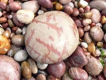 在海滩的五颜六色的被仿造的石头 免版税库存图片