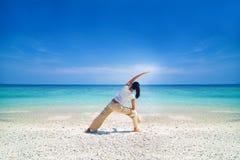在海滩的亚洲女性执行的瑜伽 免版税库存图片