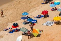 在海滩的人和太阳遮阳伞 免版税库存照片