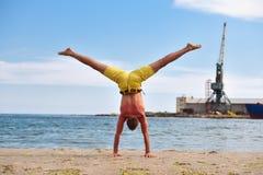 年轻在海滩的人实践的瑜伽 库存照片