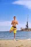 年轻在海滩的人实践的瑜伽 免版税图库摄影