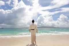 年轻在海滩的人实践的空手道 图库摄影