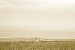 在海滩的偏僻的木码头与日落的风平浪静与乌贼属作用 库存照片