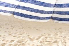 在海滩的偏僻的白色和蓝色小条伞 库存照片
