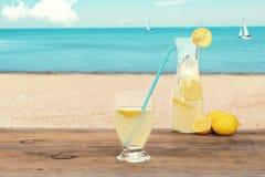 在海滩的冰冷的柠檬水 免版税库存照片