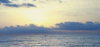 在海滩的划皮船的日出 免版税库存图片