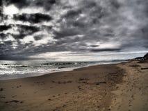 在海滩的剧烈的风雨如磐的天空 库存图片