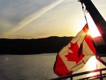 在海洋的加拿大旗子日落 图库摄影
