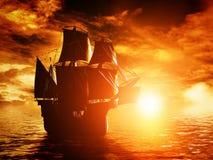 在海洋的古老海盗船航行日落的 库存图片