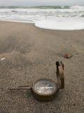 在海滩的古铜色指南针在海背景 免版税库存图片