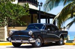 在海滩的古巴黑美国经典汽车 库存图片