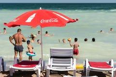 在海滩的可口可乐伞 免版税图库摄影